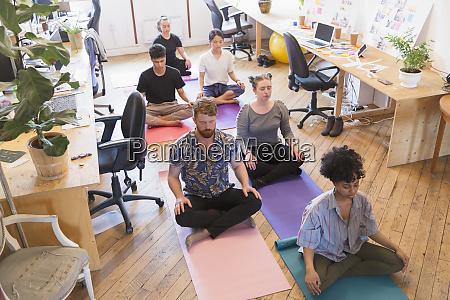 serene creative business people meditating in