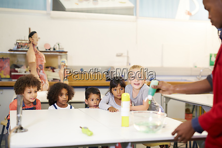 curious kids watching science experiment in