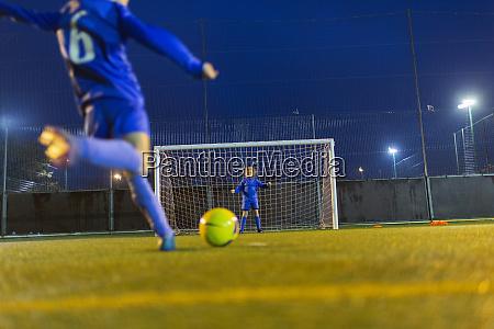 girl soccer player kicking ball toward