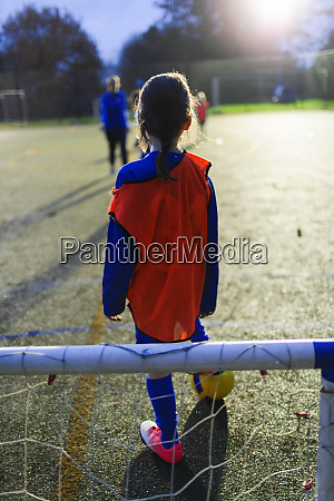 girl playing soccer on field at