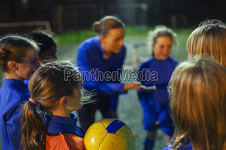girl soccer players listening to coach