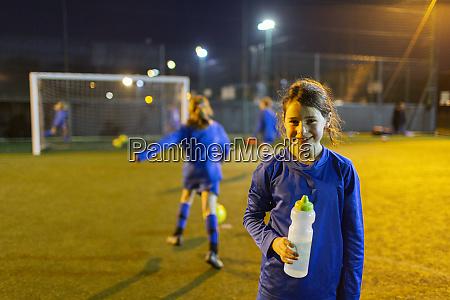 portrait smiling girl soccer player drinking