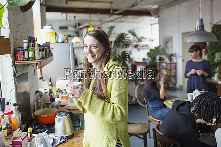 smiling young woman drinking coffee with