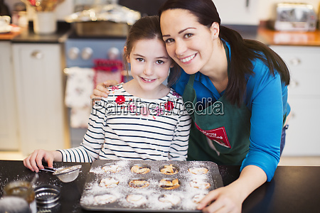 portrait smiling mother and daughter baking