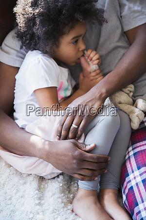 father cuddling innocent girl sucking thumb