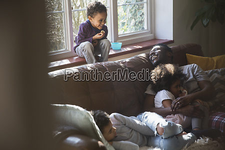 happy father and children cuddling on