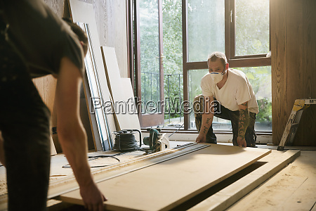 construction workers lifting wood board in