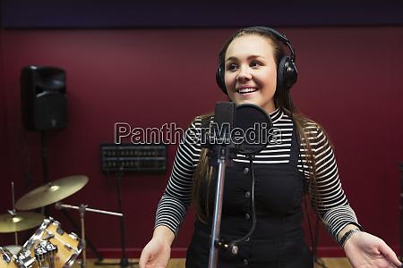confident teenage girl recording music singing