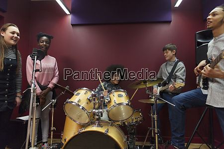 teenage musicians recording music in sound