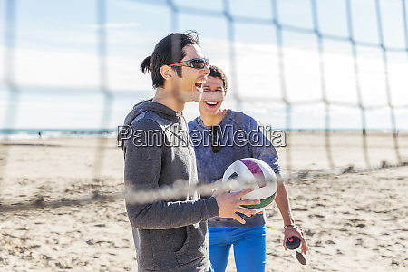 happy male friends playing beach volleyball