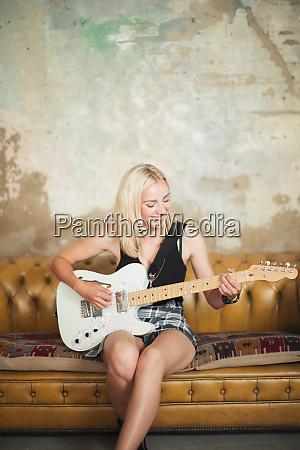 young woman playing electric guitar on