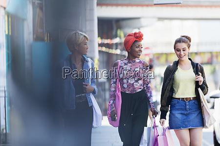 young women friends walking with shopping