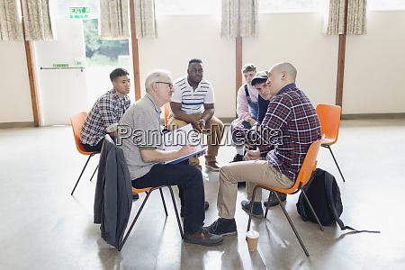 men talking in circle in group