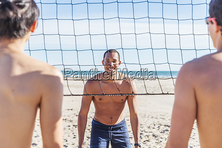 portrait confident man playing beach volleyball