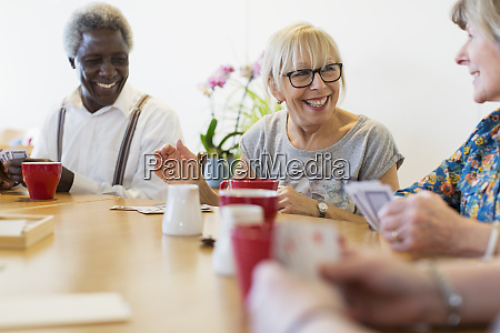 happy senior friends playing cards at
