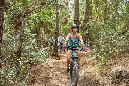 carefree woman mountain biking on trail