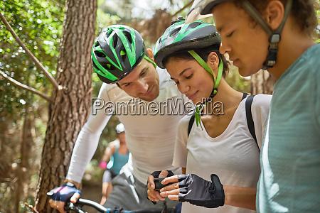 friends mountain biking checking wearable camera