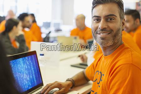 portrait confident hacker at laptop coding