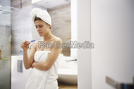 young woman in bathroom worrying over