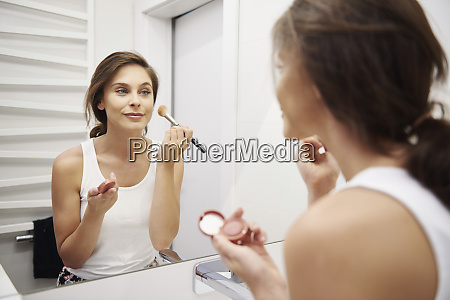 mirror image of smiling young woman