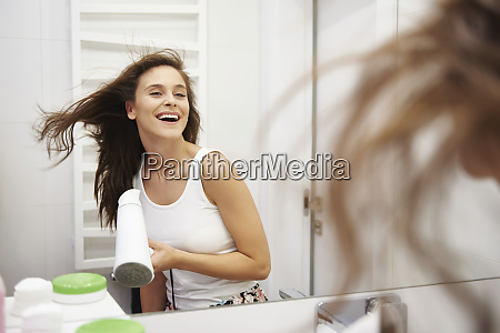 mirror image of laughing woman blow