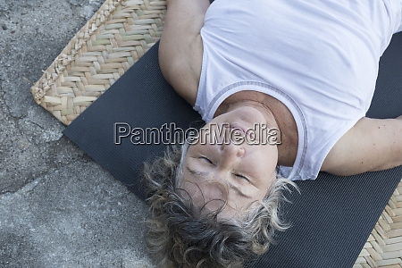 senior woman lying on yoga mat