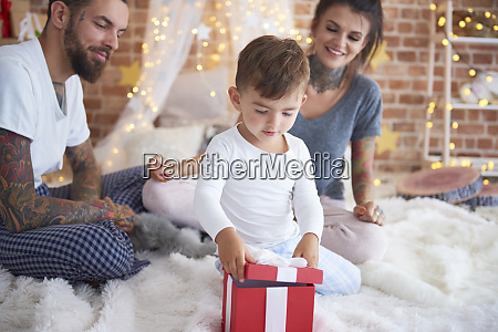 boy opening christmas present with his