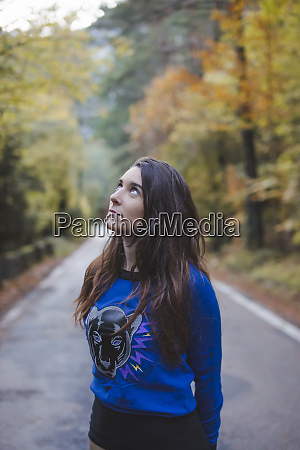 young woman standing on country road