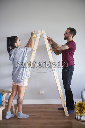 modern couple decorating the home at