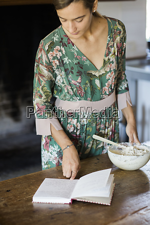 young woman preparing cake dough looking