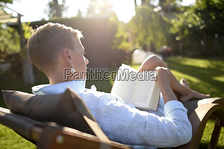 woman on deckchair reading book in