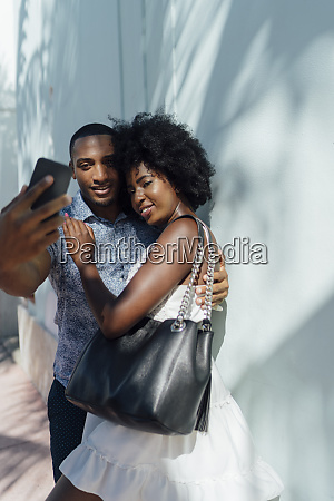smiling young couple embracing and taking