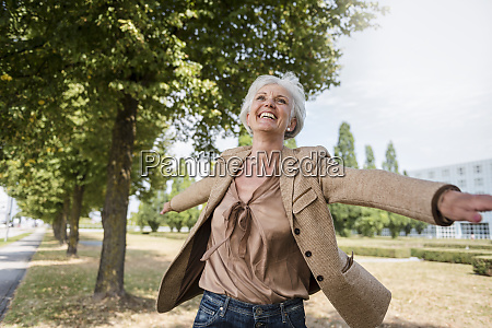 happy senior woman with outstretched arms