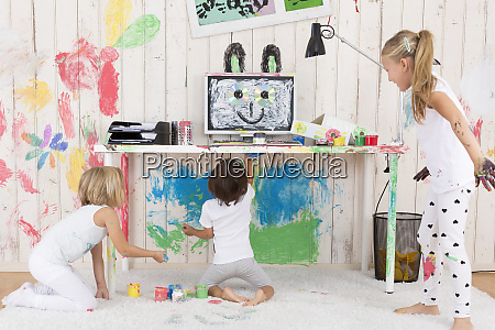 three girls painting office with finger