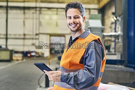 portrait of smiling man holding tablet