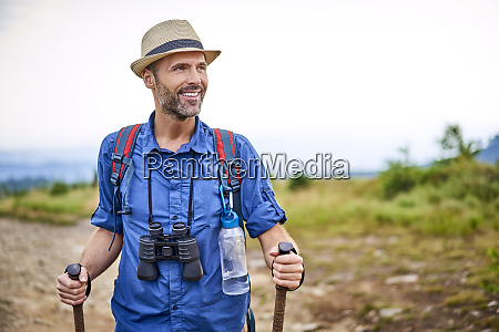 smiling man with binoculars hiking in