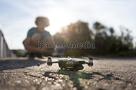 boy landing his drone on the