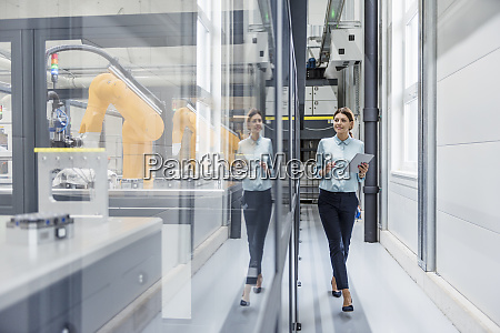 businesswoman checking robots with digital tablet