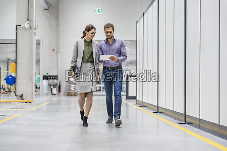 businessman and woman walking in company
