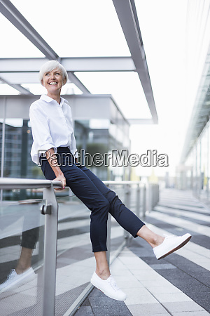 happy senior woman sitting on railing