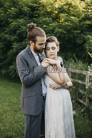 bride embracing groom on a meadow