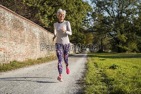 senior woman running along brick wall