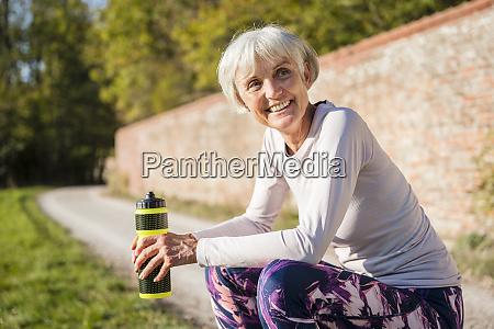 smiling sportive senior woman holding bottle