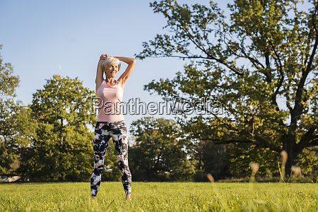 senior woman stretching on rural meadow