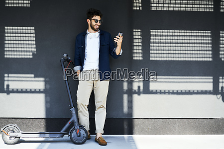 smiling young man with electric scooter