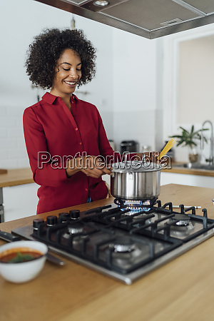 woman standing in kitchen preparing food