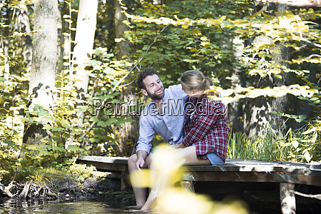 young couple sitting on a bridge