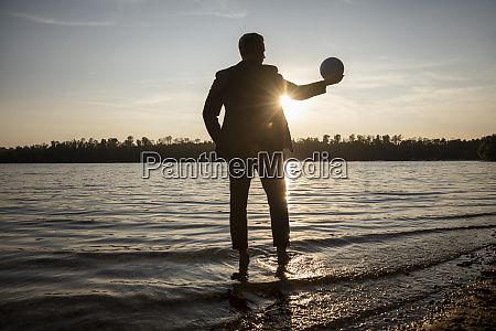 silhouette of businessman standing at lakeshore