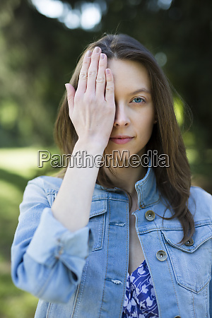 portrait of young woman outdoors covering