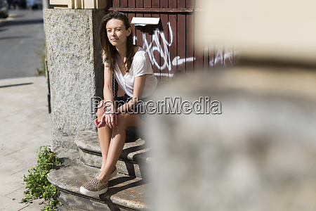 smiling young woman sitting on stairs